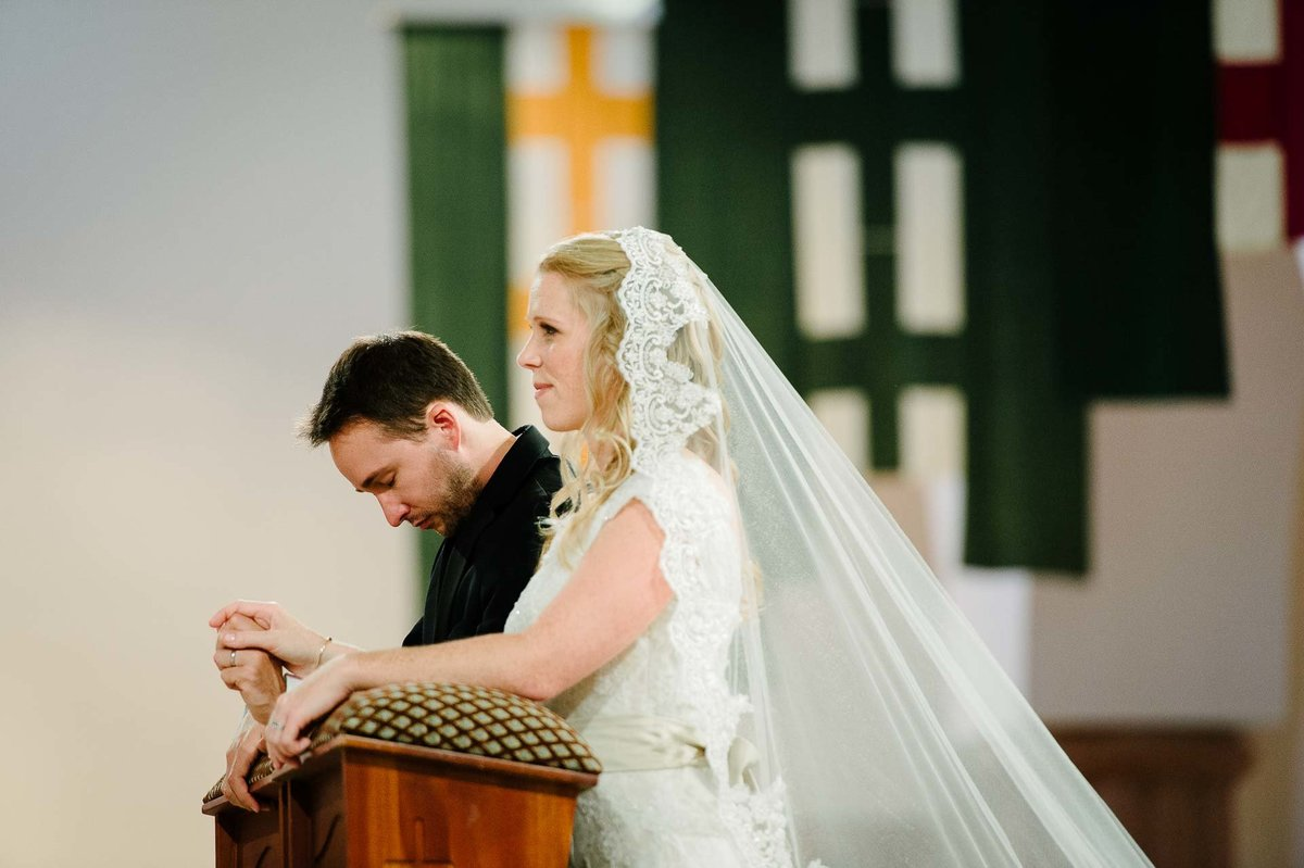 bride and groom praying at saint ann church during wedding ceremony
