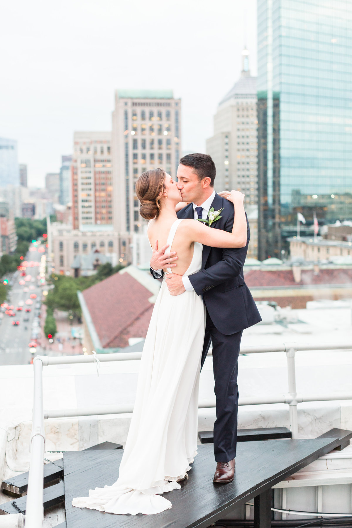 Bride and groom kissing on rooftop at the Lenox Hotel