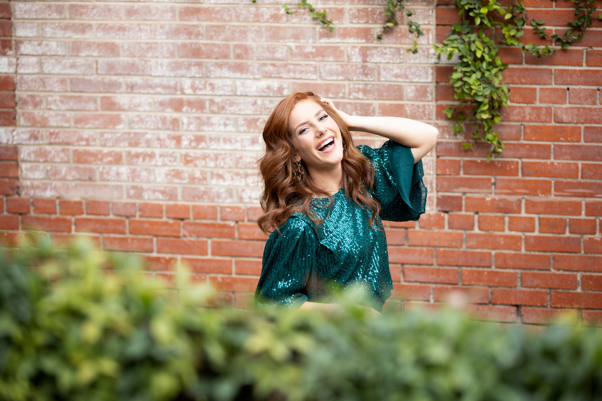 Girl smiling wearing a green sequins top and red hair