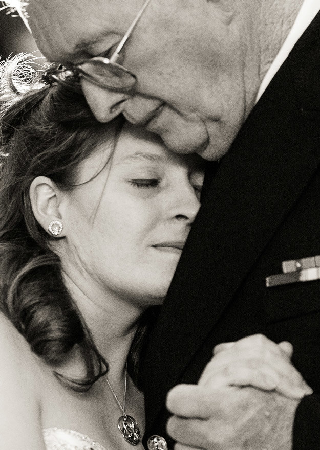The bride comfortably hugs her dad during their Father-Daughter dance during a reception in Decatur, Illinois.