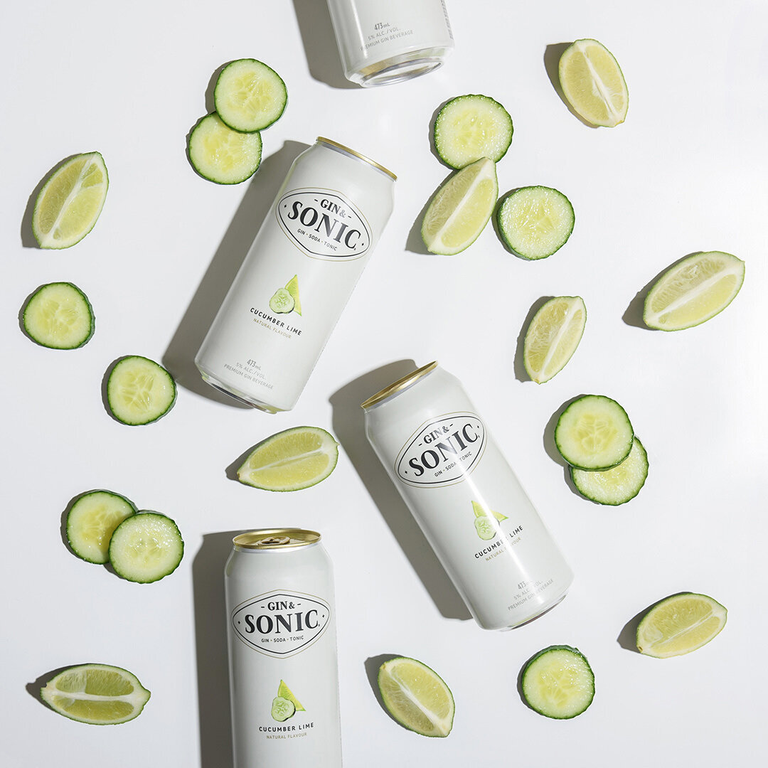 gin and tonic canned beverage with limes and cucumber