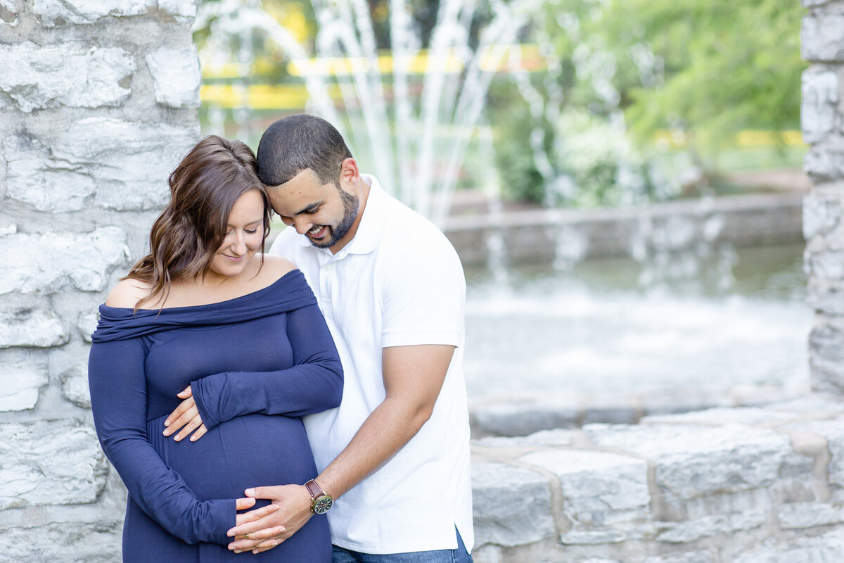 Spring Maternity Session with blue maxi dress standing by fountain  at Oak Knoll Park in St. Louis by Amy Britton Photography Photographer  in St. Louis