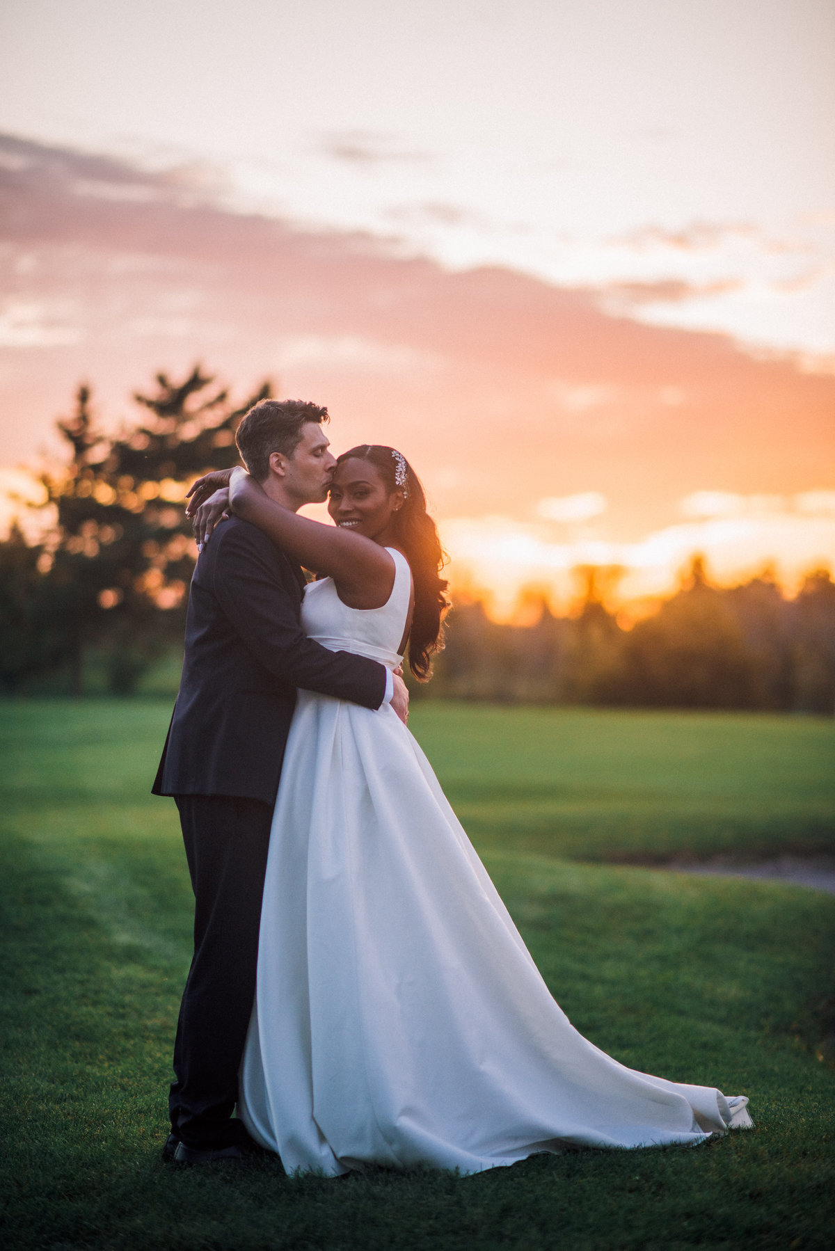 bride and groom pose in front of the setting sun