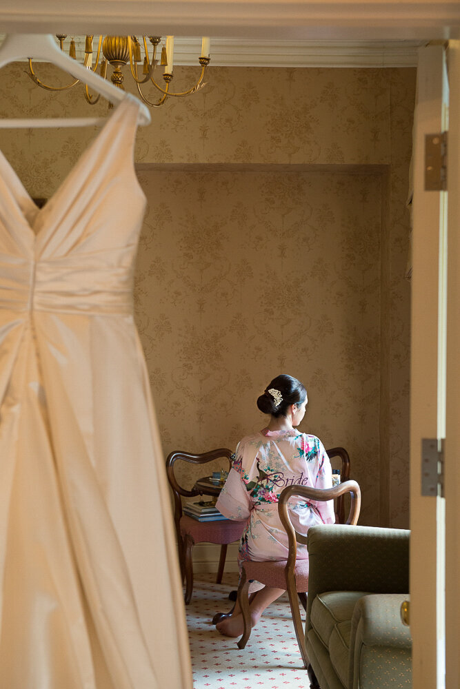 brunette bride wearing a headpiece and floral pink kimono style dressing gown in the bridal suite of Cahernane House with her wedding dress hanging over the door