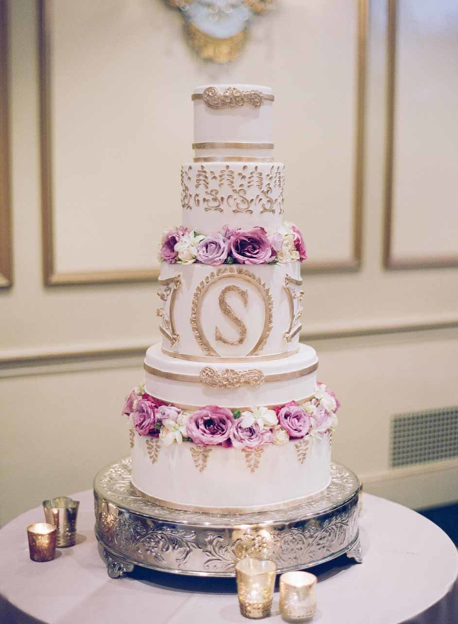 Beautiful white layer wedding cake with gold accents and purple roses.