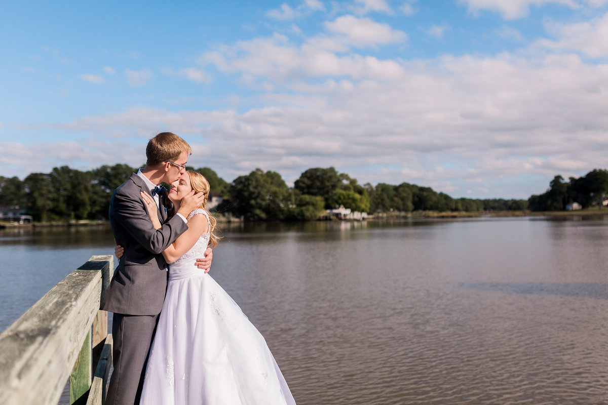 A bride and groom kiss on a dock at Fort Eustis