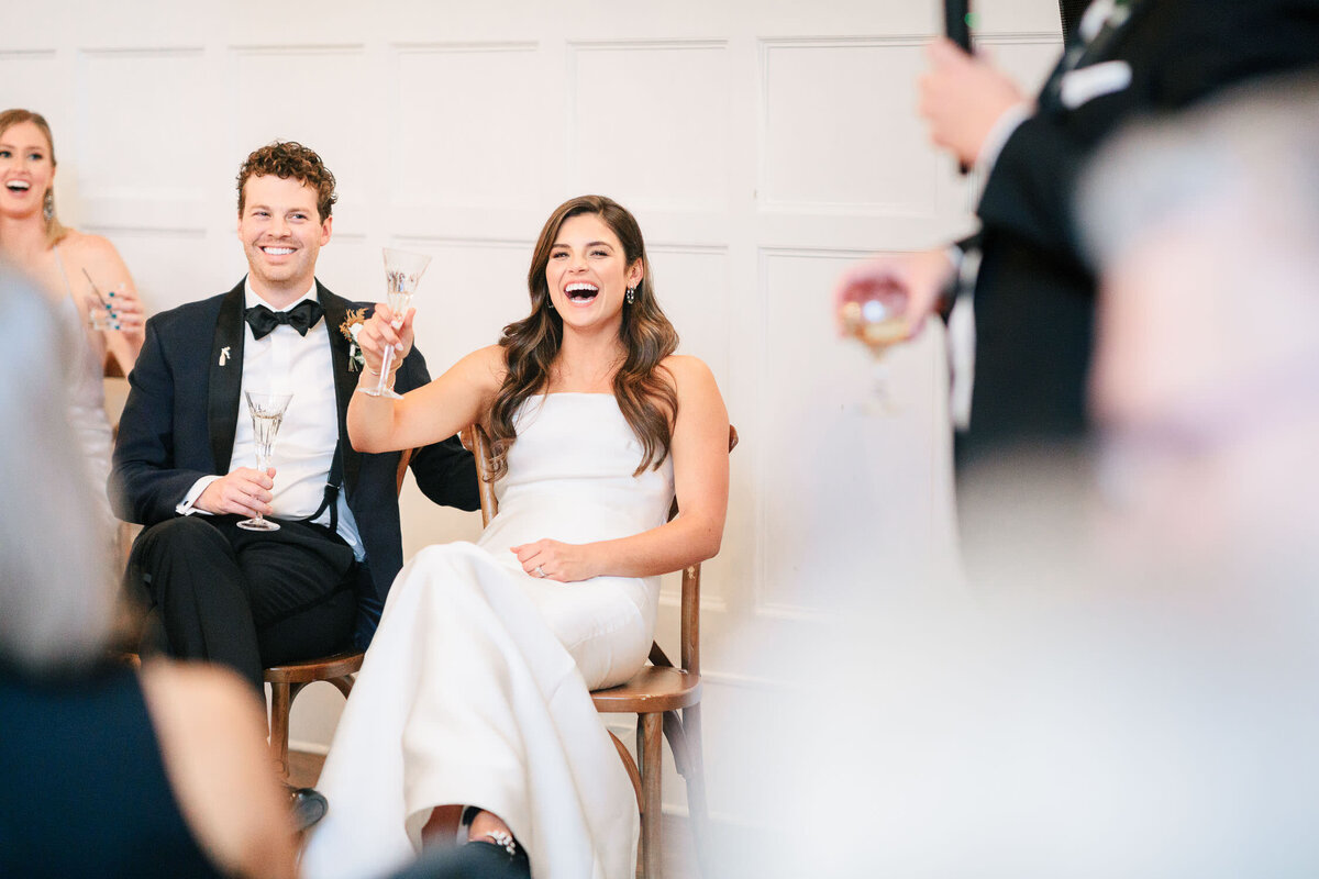 Bride and groom toasting and laughing while sitting at wedding reception