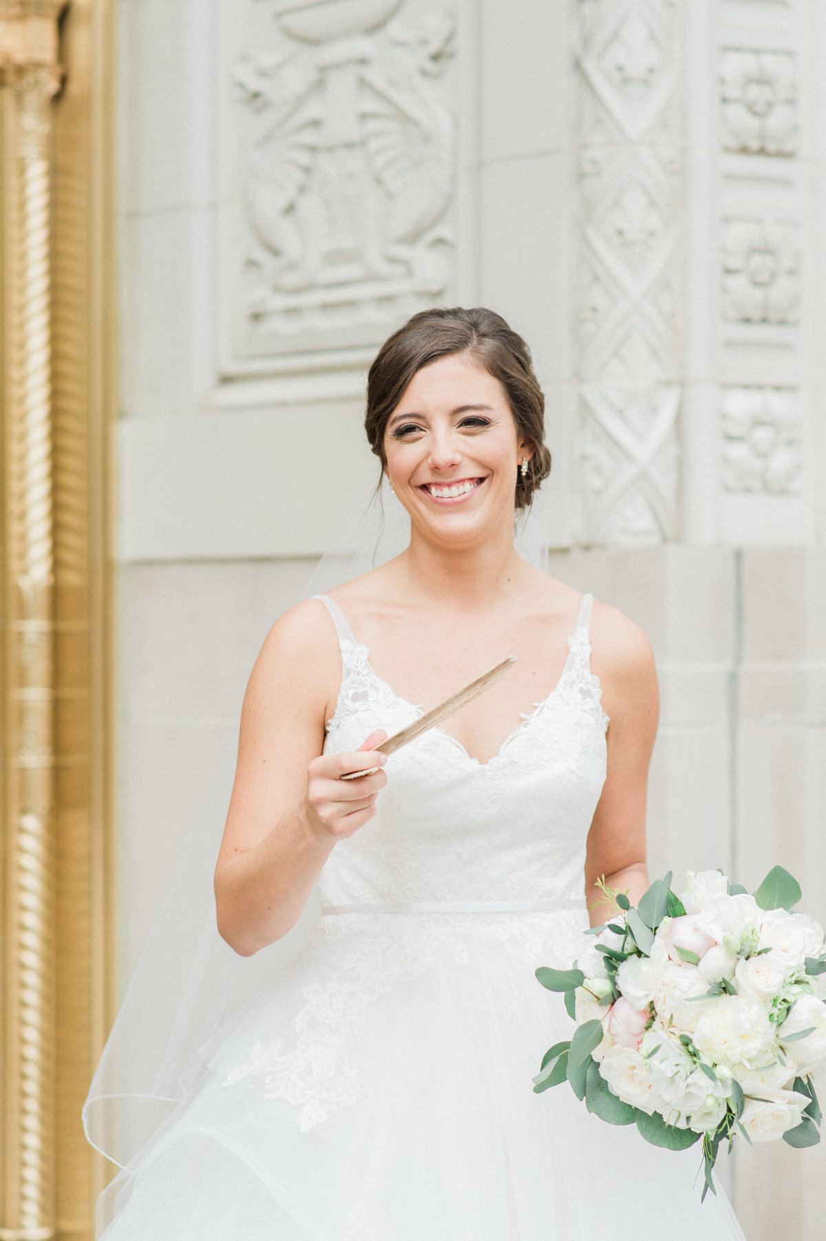 bride holding fan and smiling