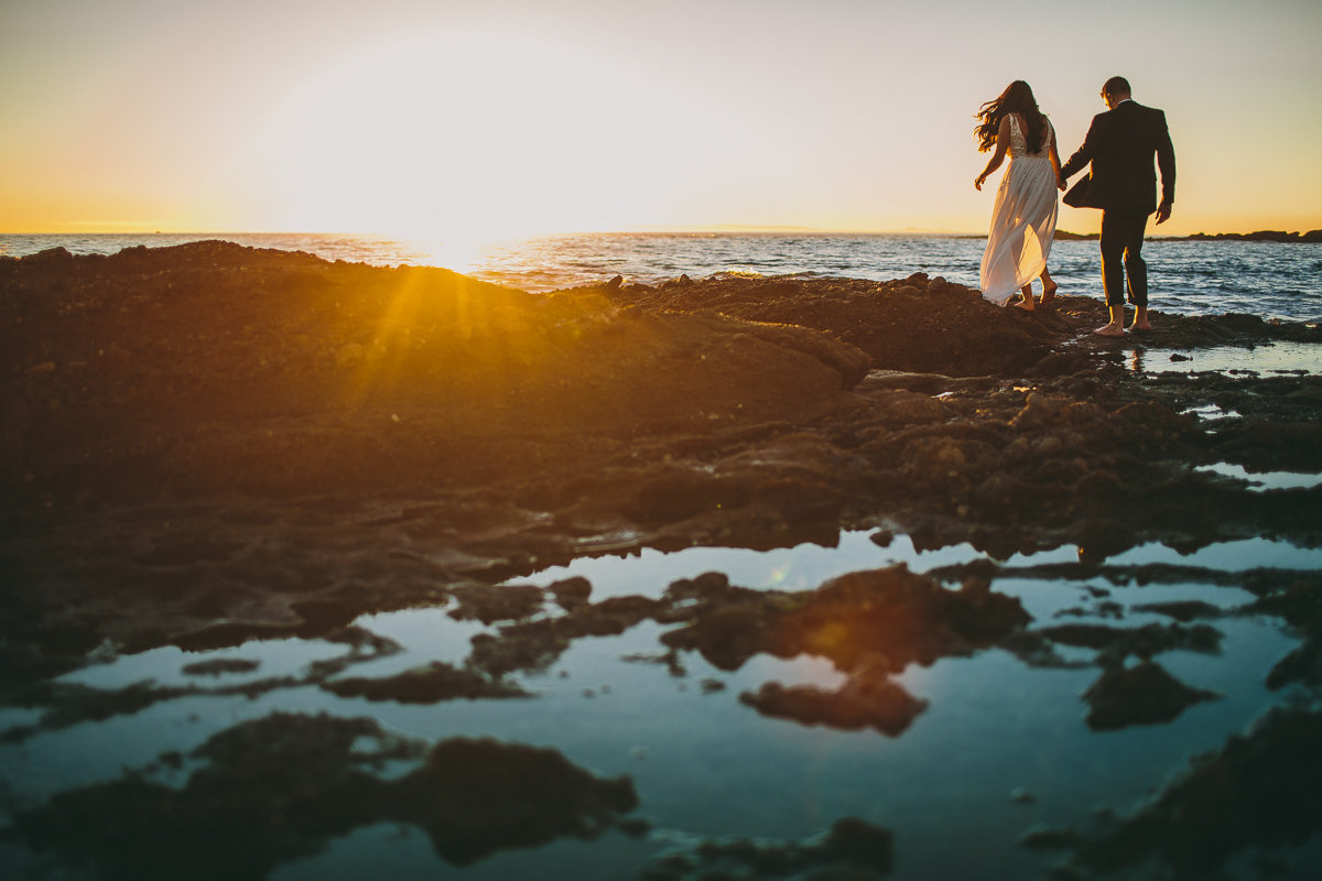 Couple walks along the rocks on the beach during their Laguna Beach engagement session.