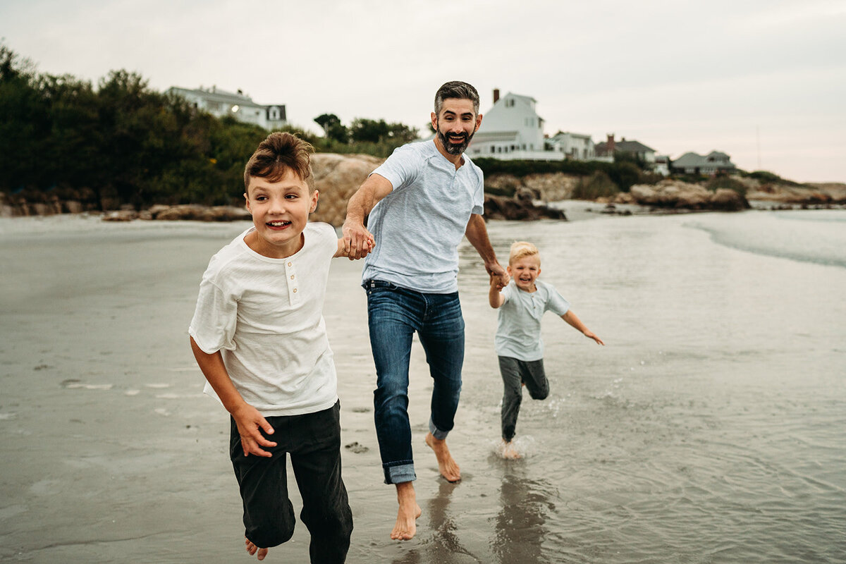 dad runs with sons across beach outside of boston massachusetts
