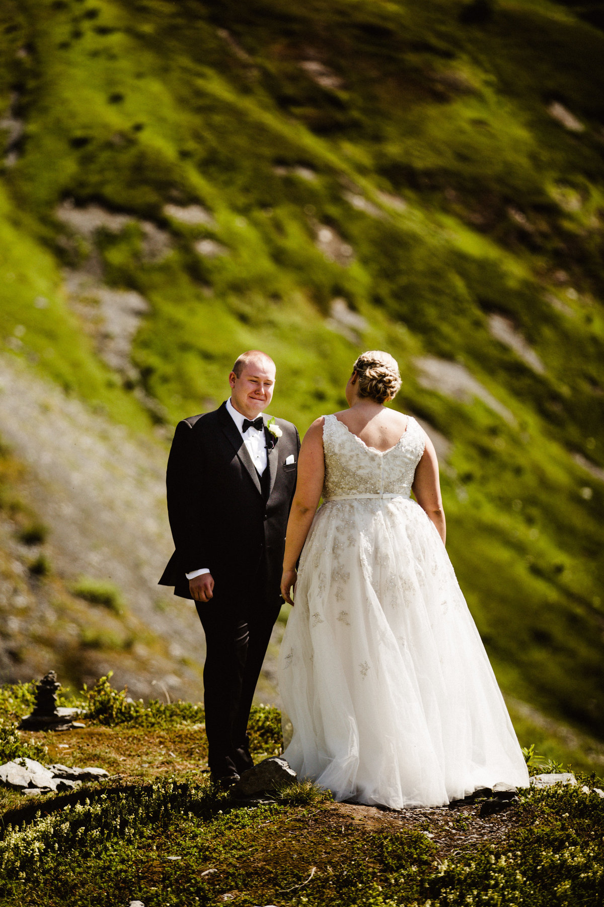 groom chokes back tears during first look on mountaintop at alyeska
