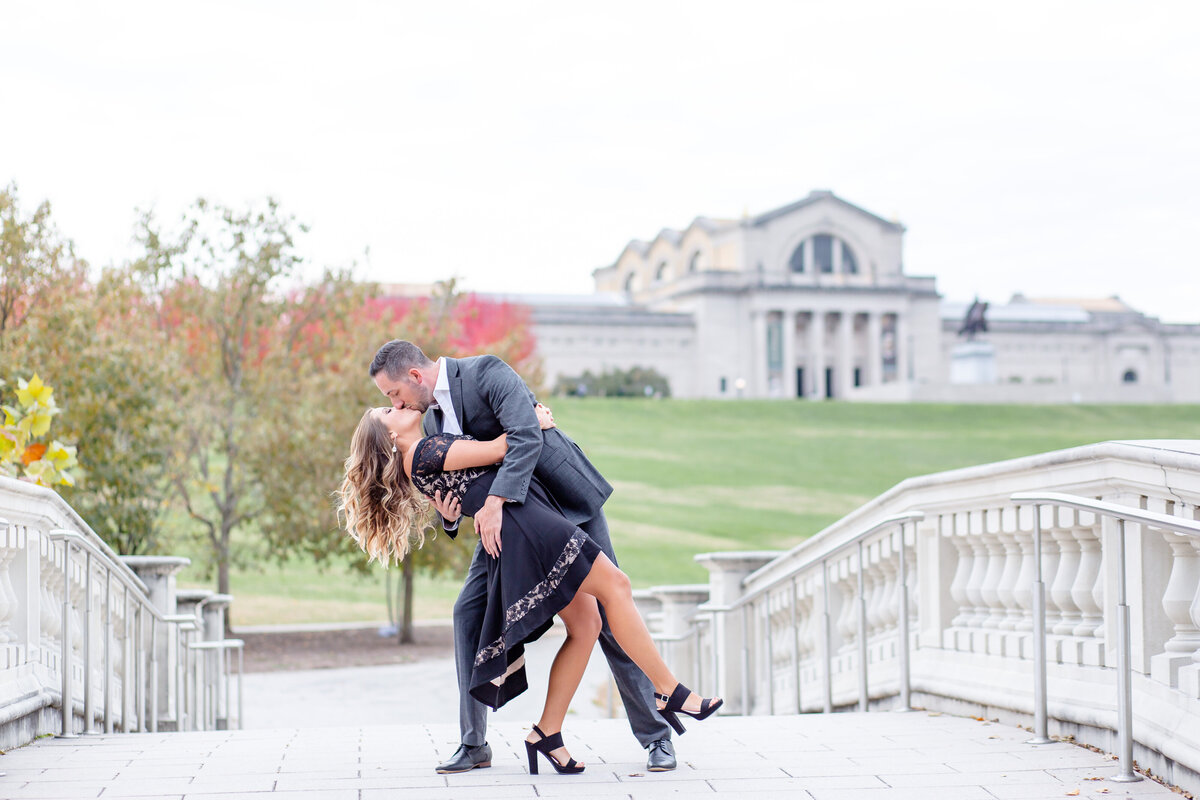 Fall Sunset Engagement  Session with black dress guy dipping girl couple kissing  on bridge at the bottom of Art Hill  in Forest Park in St. Louis by Amy Britton Photography Photographer in St. Louis