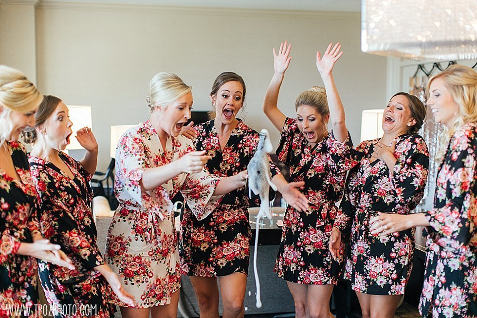 bridesmaids popping champagne bottles