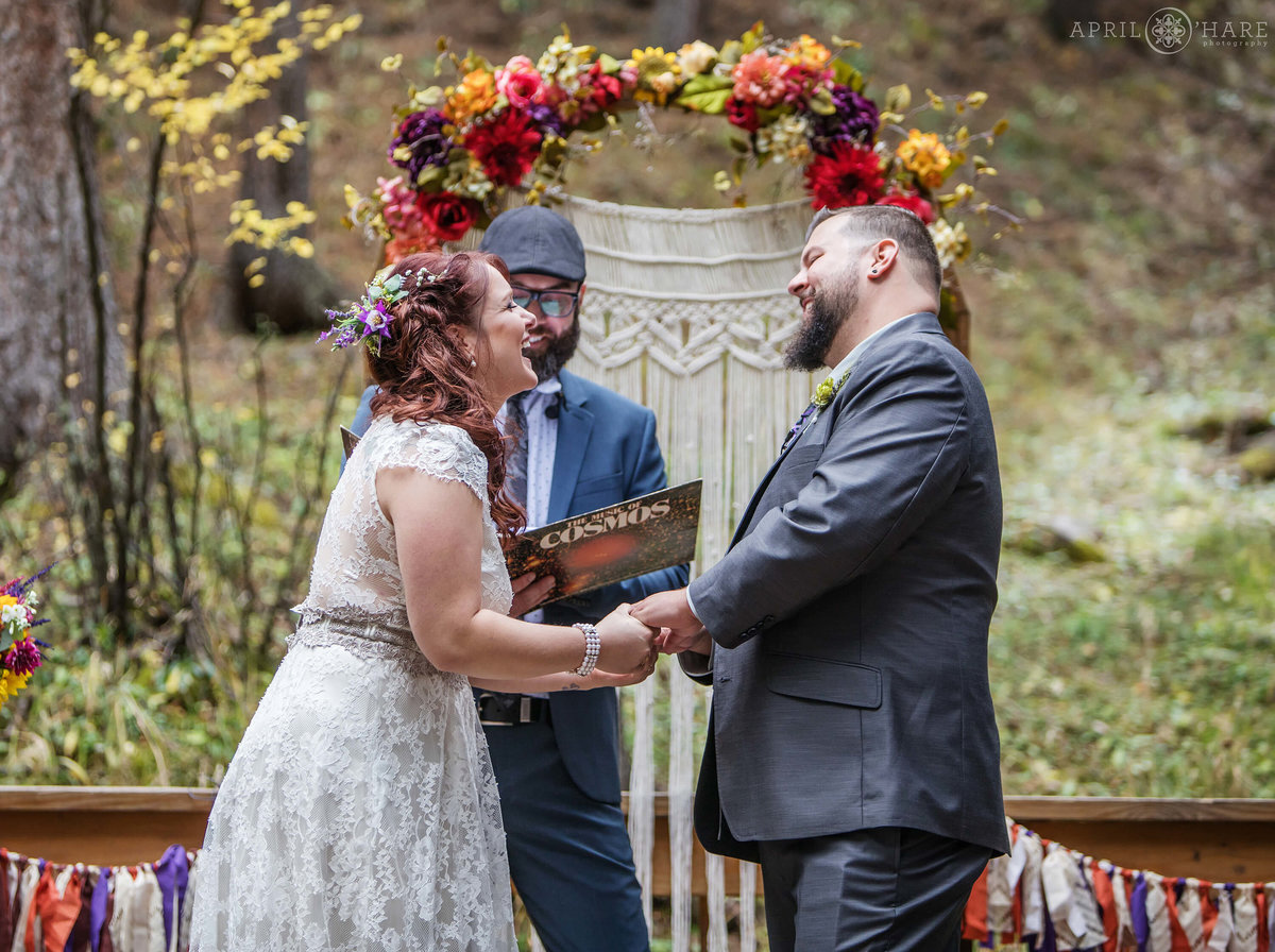 Happy couple laughing in front of their Macrame altar in the forest of Colorado at Beaver Ranch in Conifer