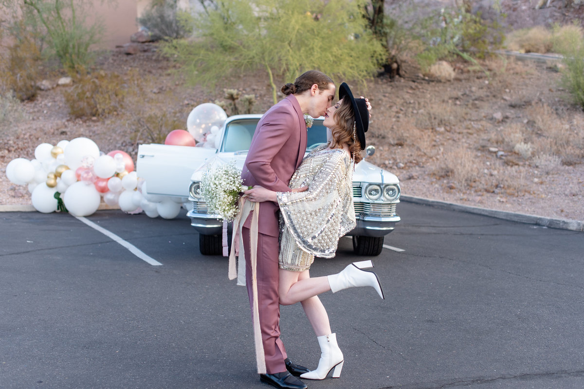 eloped couple kiss in front of vintage car