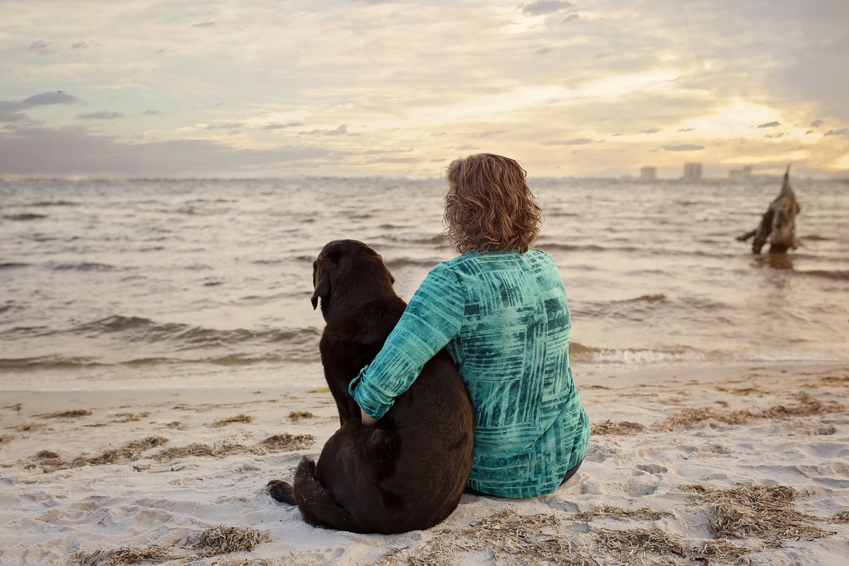 Black lab dog and owner beach sunset