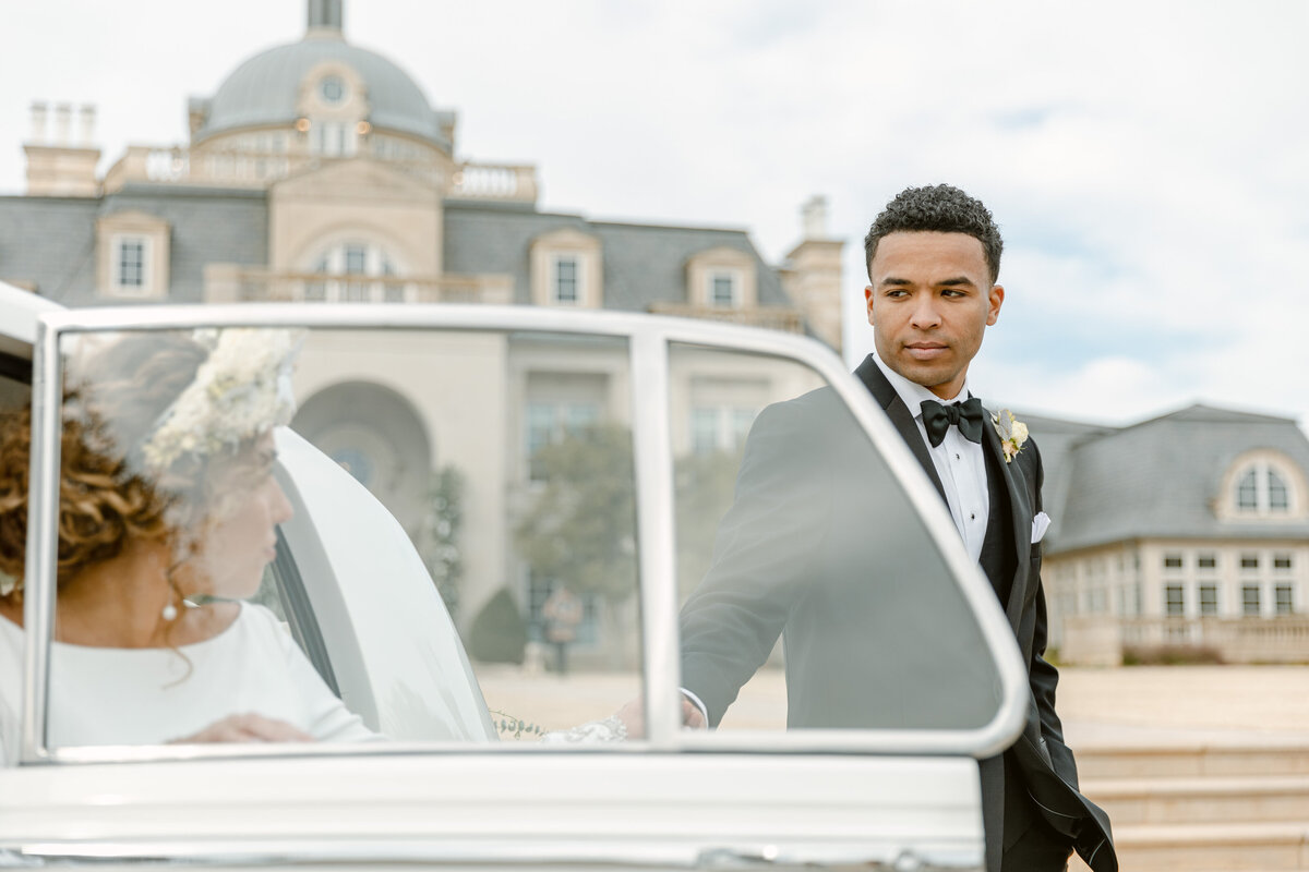 Handsome groom in tux helps his bride out of a white Rolls Royce outside of their chateau wedding venue