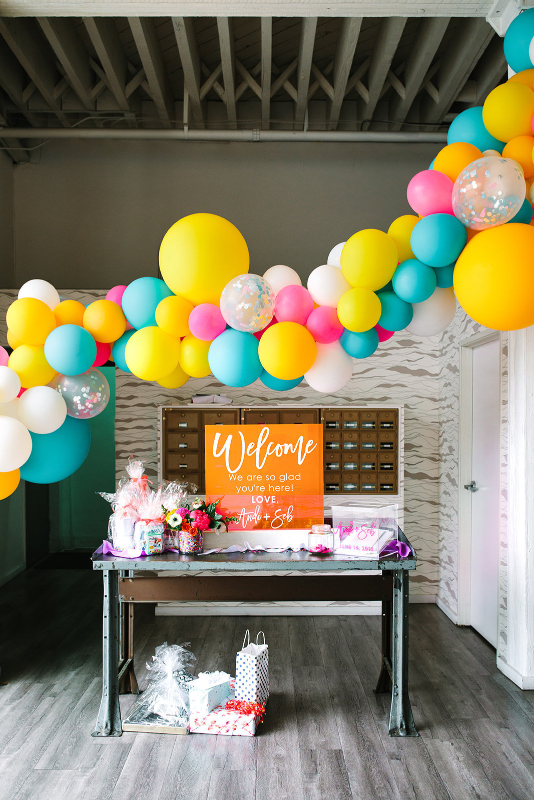 Wedding welcome table with neon wedding sign and colorful ballon garland at The Unique Space LA in downtown Los Angeles