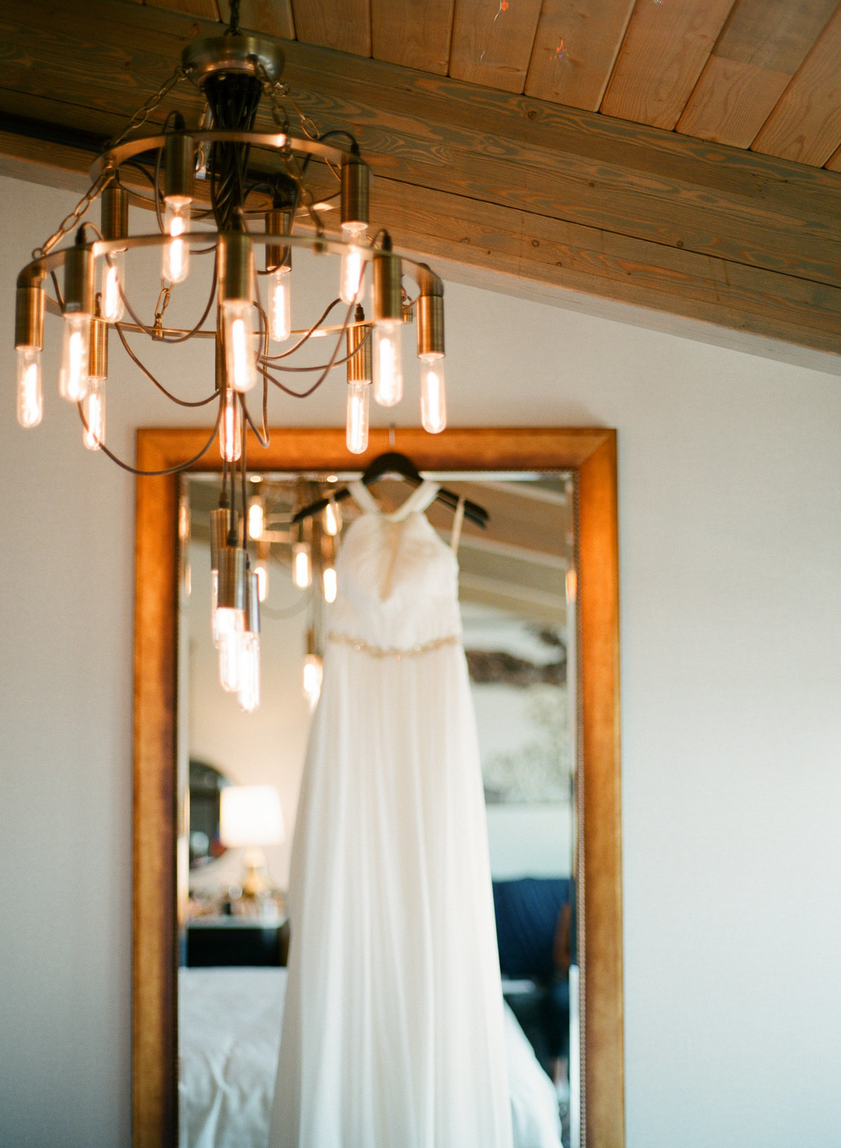 wedding day details dress hanging on mirror in charmant hotel edison bulb chandellier