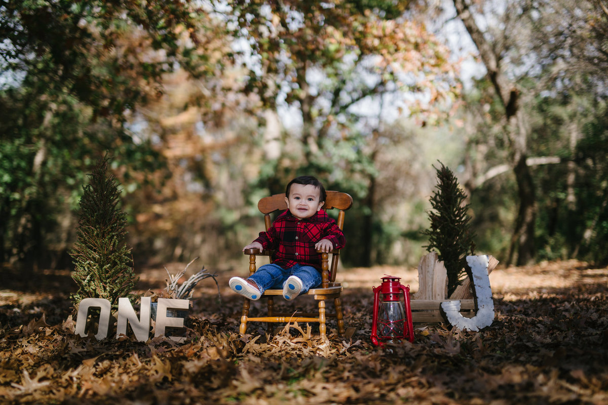 Baby one year picture in rocking chair one in a forrest of leaves with photography props at Denman Estate Park in San Antonio