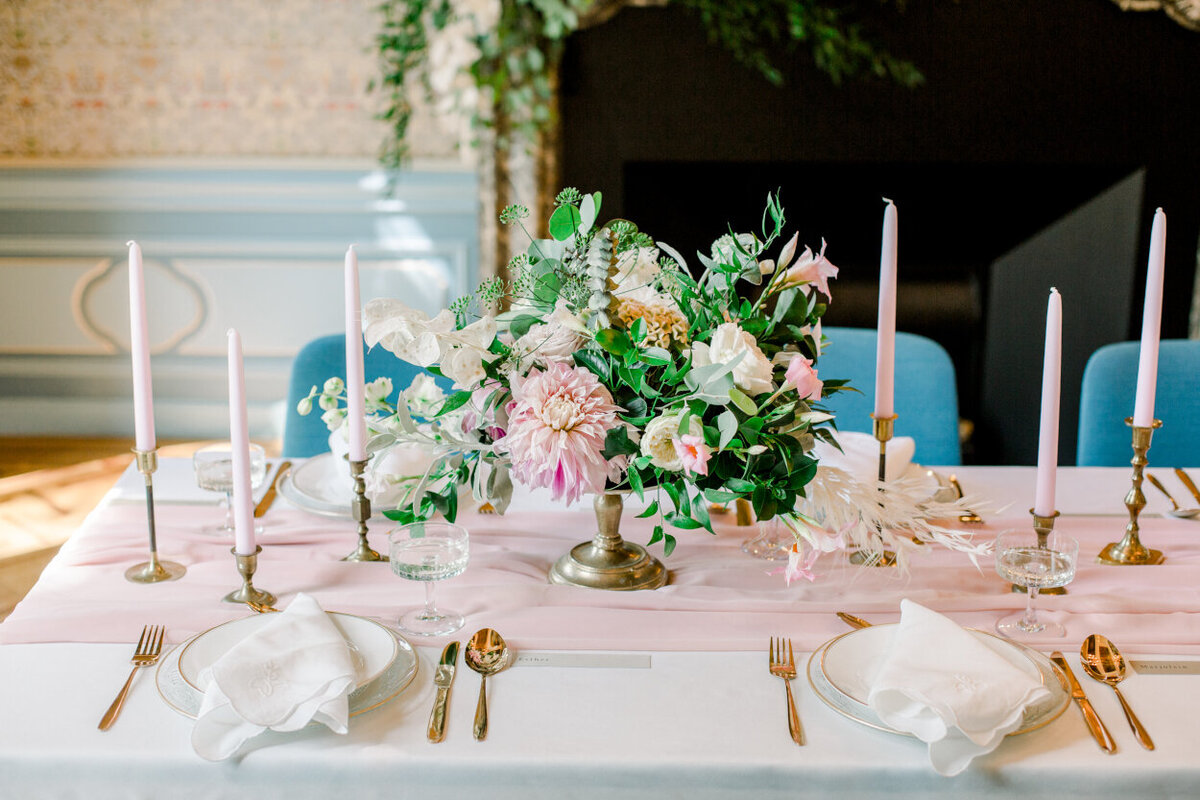 Tablescape with a lush blush floral centerpiece, tapers, golden cutlery, and vintage napkins for an intimate wedding photoshoot at the Tassenmuseum organized by Lovely & Planned