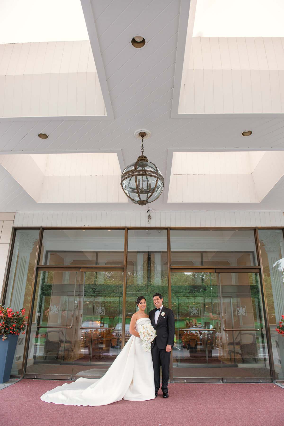 wedding photo of bride and groom standing at the front entrance of The Garden City Hotel