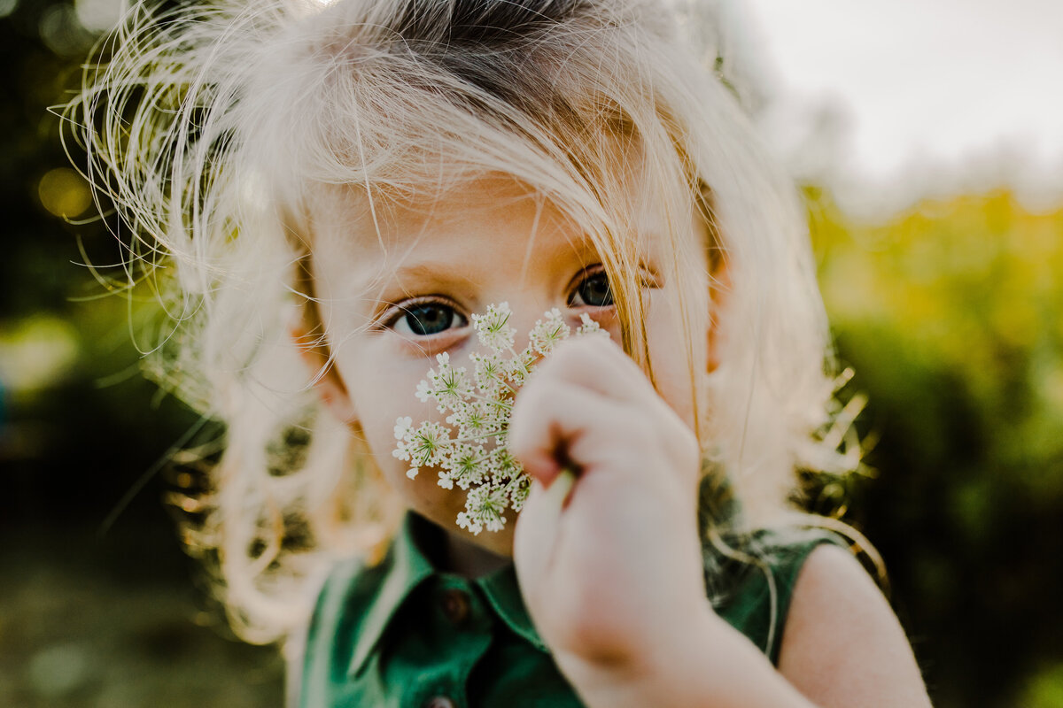 little blonde girl smelling a wildflower