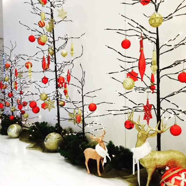 light trees decorated with red and gold ornaments for corporate office holiday decorations with gold reindeer