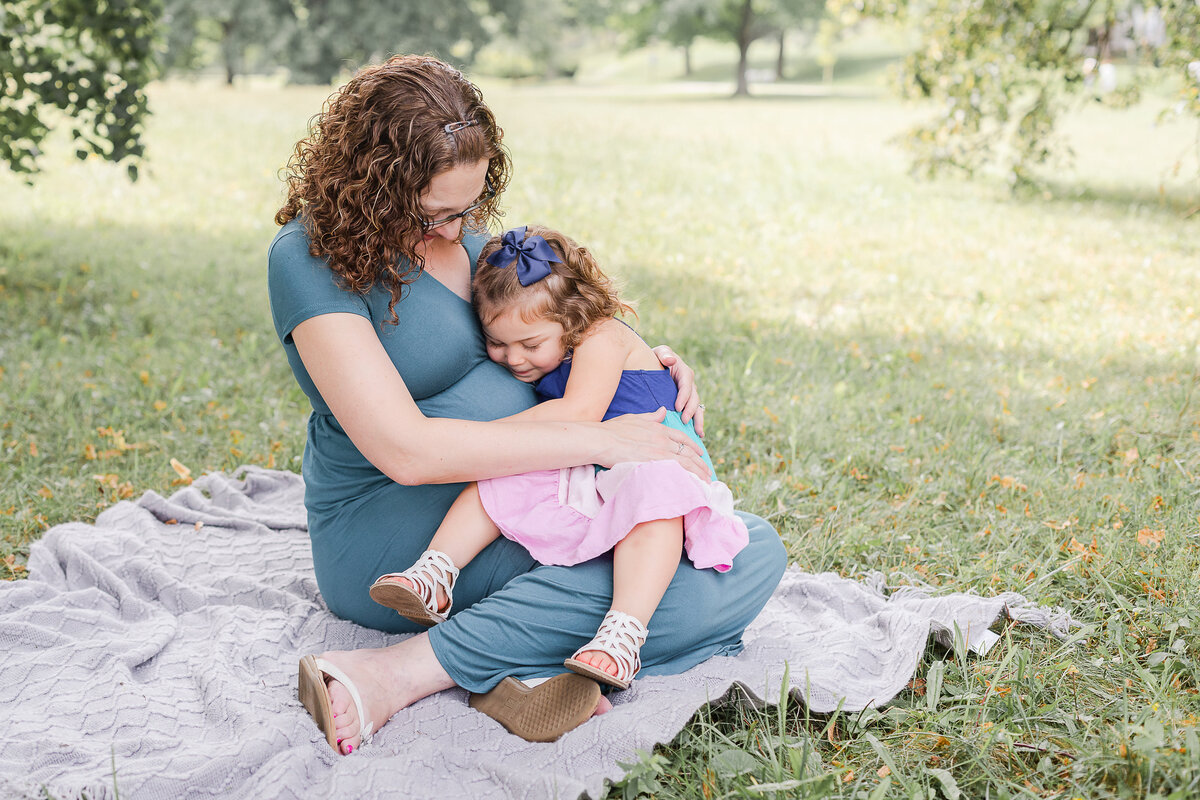 daughter sits on pregnant mom's lap during maternity photos Cushing Memorial Park Framingham MA