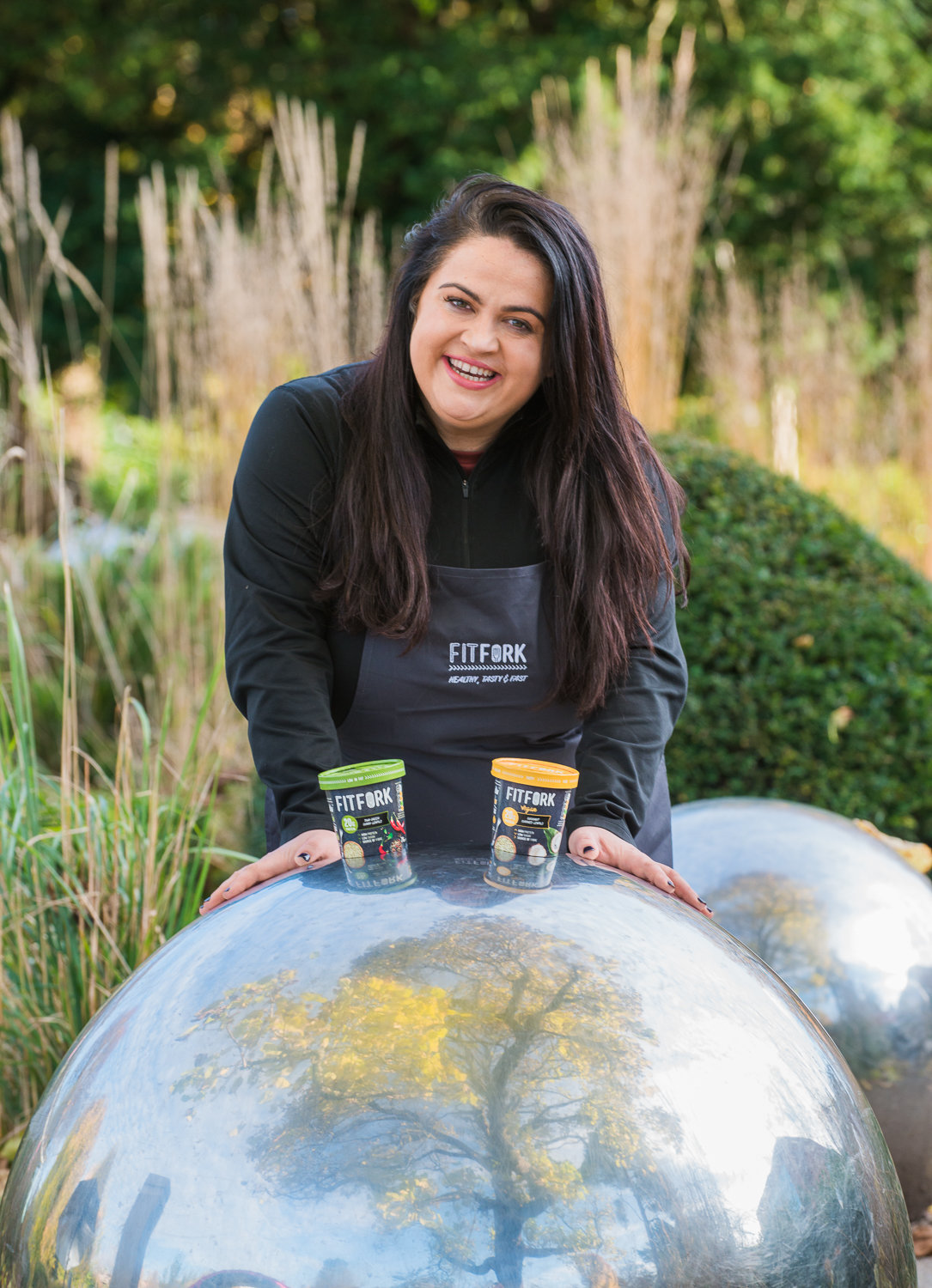 Female chef with black hair in a park promoting healthy food