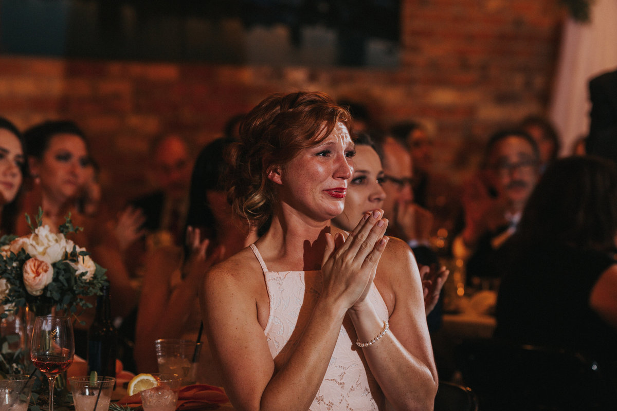 A brides sister cries as she watches her sister dance at the reception
