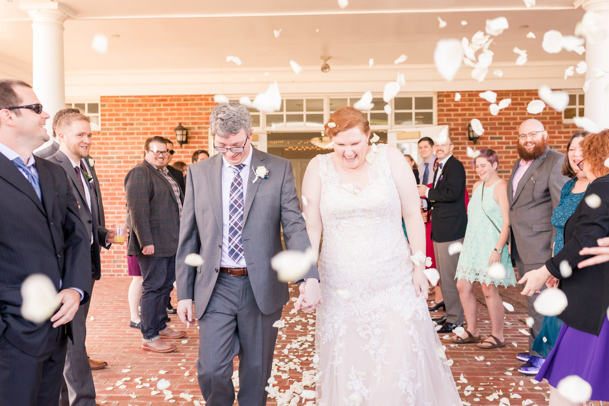 A bride and groom exit in a shower of petals at Ospreys at Belmont Bay in Woodbridge