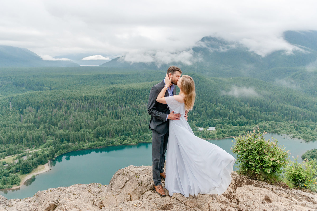Tall man kisses blonde woman wearing a flowing blue dress on top of Rattlesnake Ridge just outside of Seattle