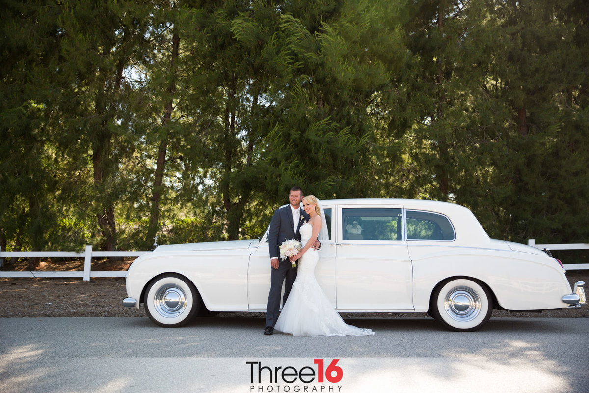 Newly married couple posing in front of classic car