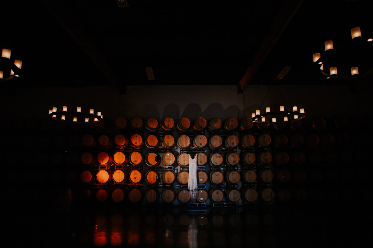 Callaway Winery Temecula wedding pictures bride's dress hangs in barrel room