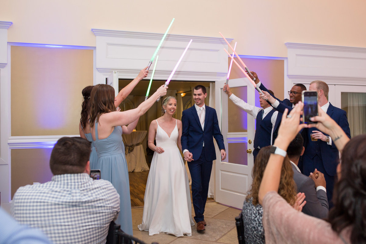 bride and groom walking under neath light sabers for first dance