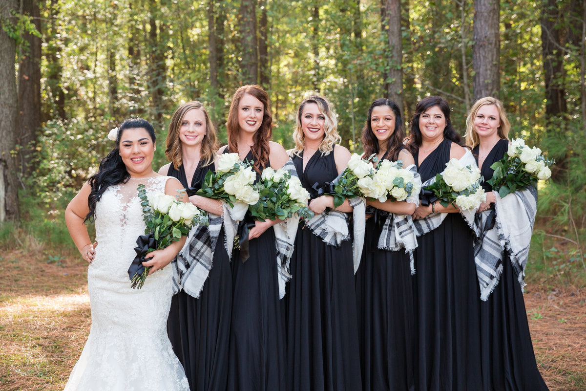 bride and bridesmaids in the woods wearing black bridesmaids dresses with white rose bouquets
