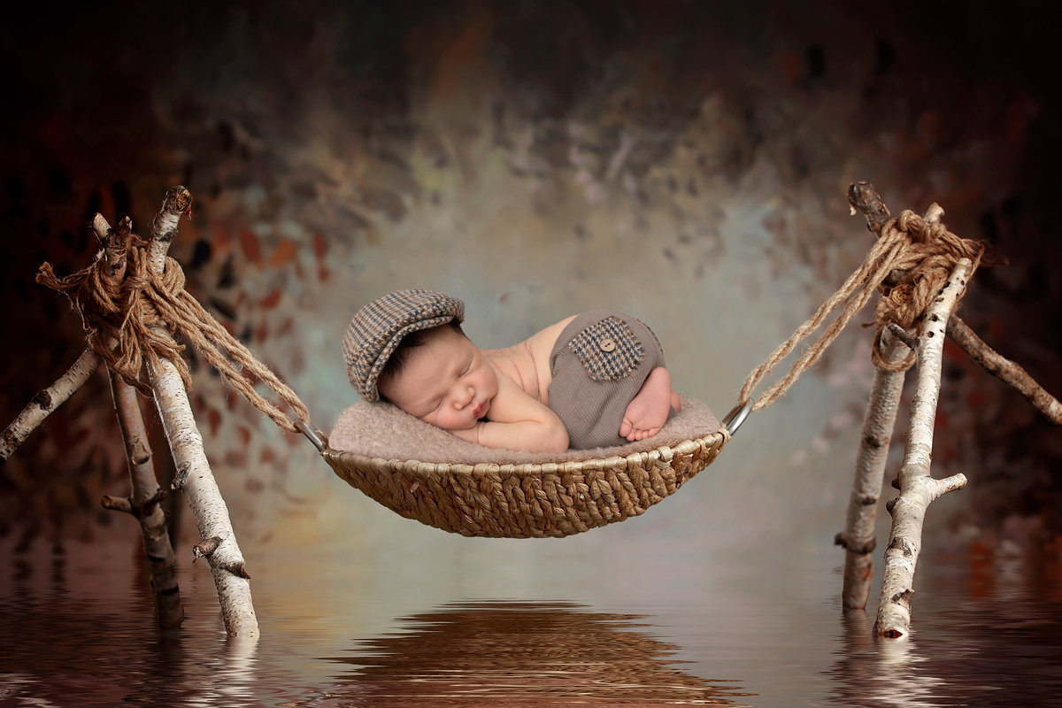 Newborn boy in a swing over water