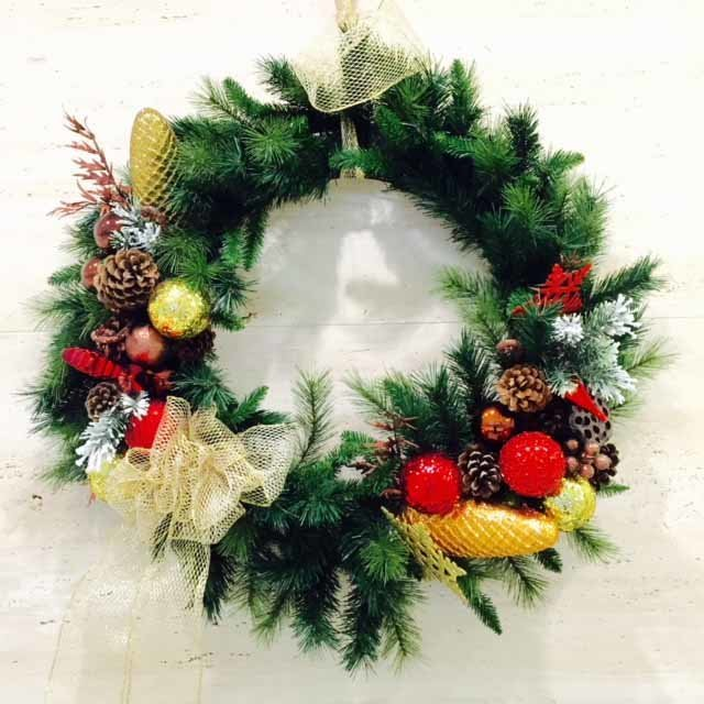 wall wreath for holidays with evergreen, red and gold ornaments, and acorns