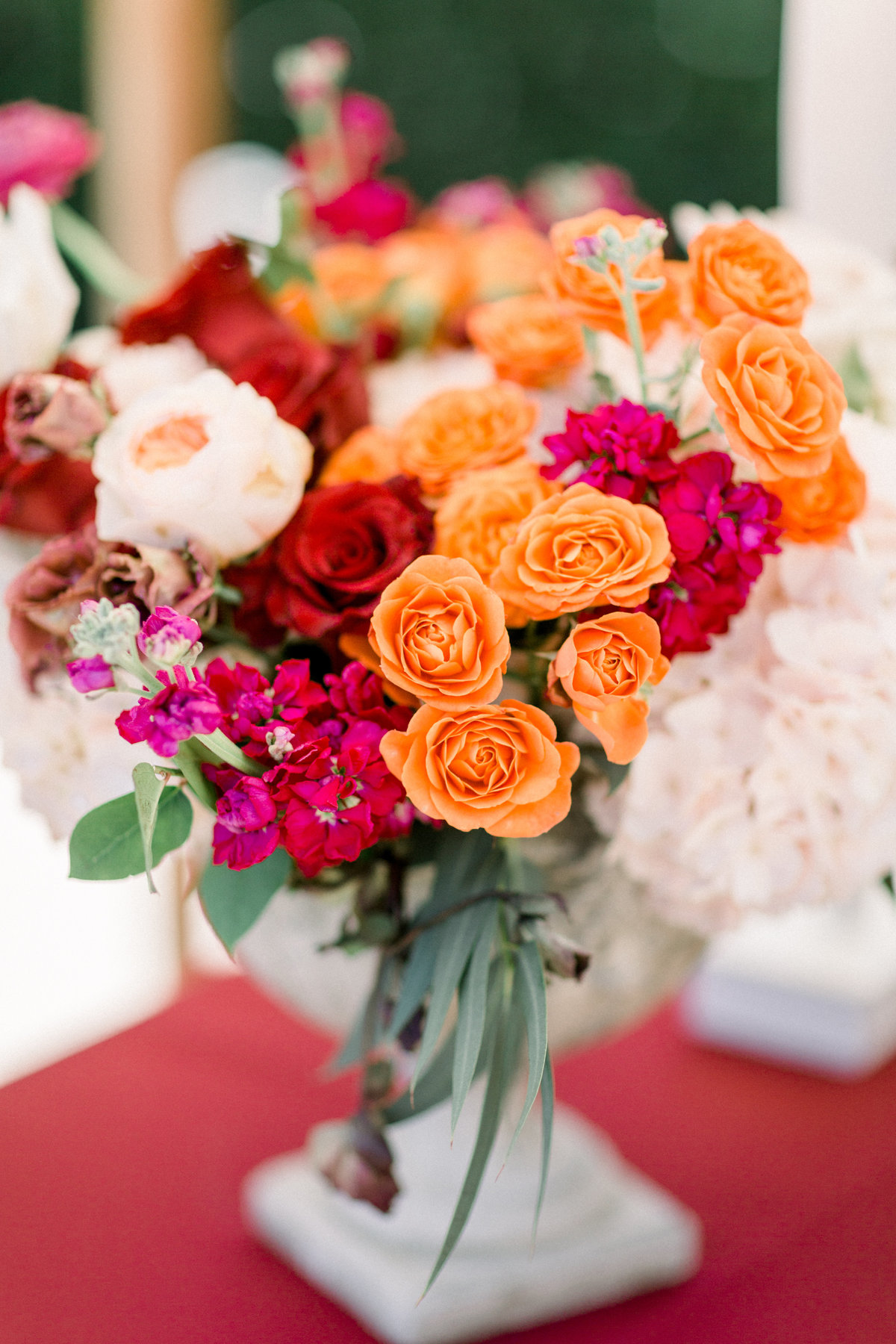 Wedding floral centerpiece with orange and mauve flowers at Maravilla Gardens wedding