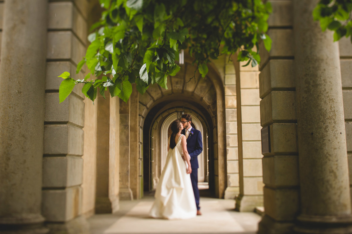 the bride and groom under an archway at cliveden house