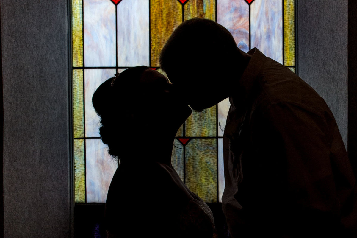 backlit bride and groom share kiss