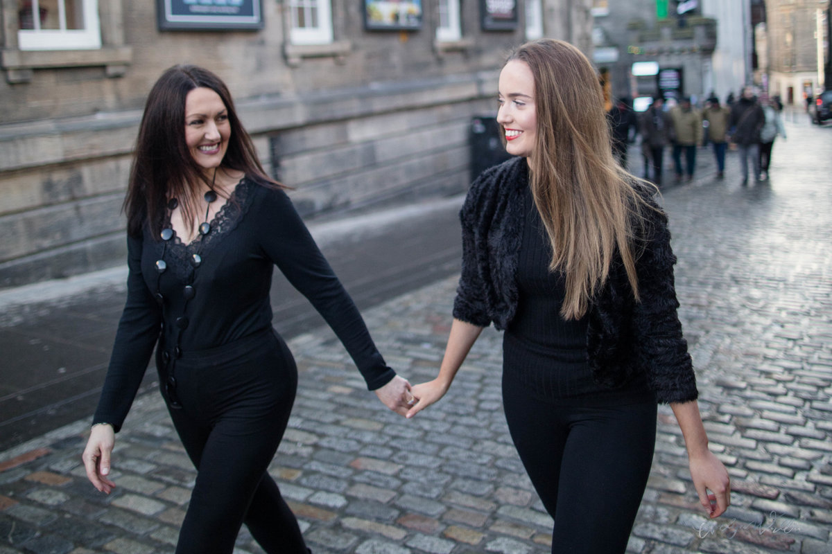 Mother and daughter holding hands, walking on the Royal Mile Edinburgh, Scotland