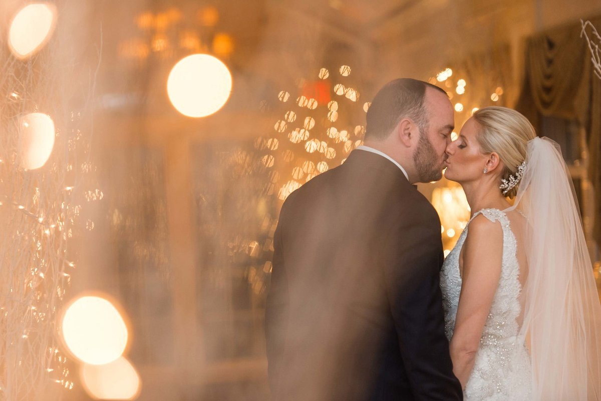 Bride and groom kissing in the hallway of Bridgeview Yacht Club