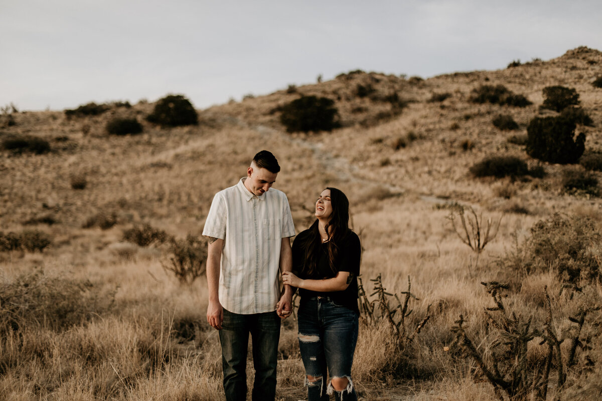 engaged couple walking and holding hands laughing in the desert