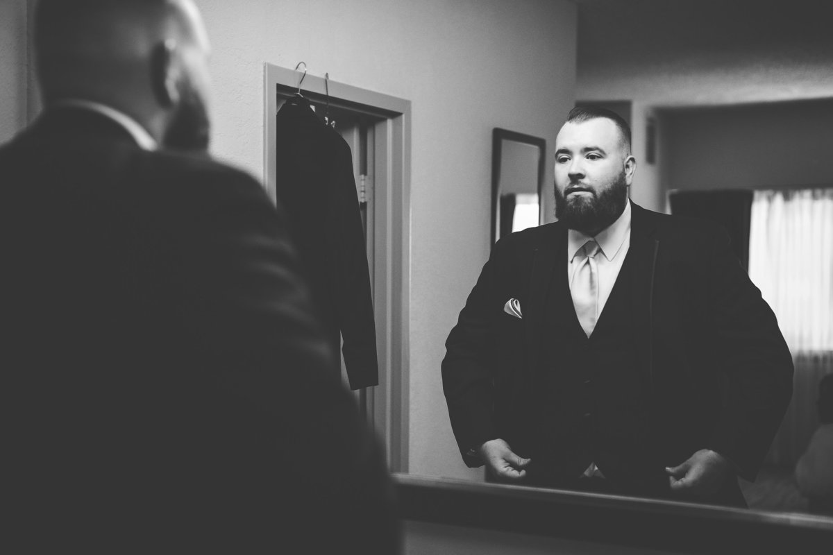 Groom Looks in the Mirror as He Gets Ready for His Tampa Bay Florida Wedding