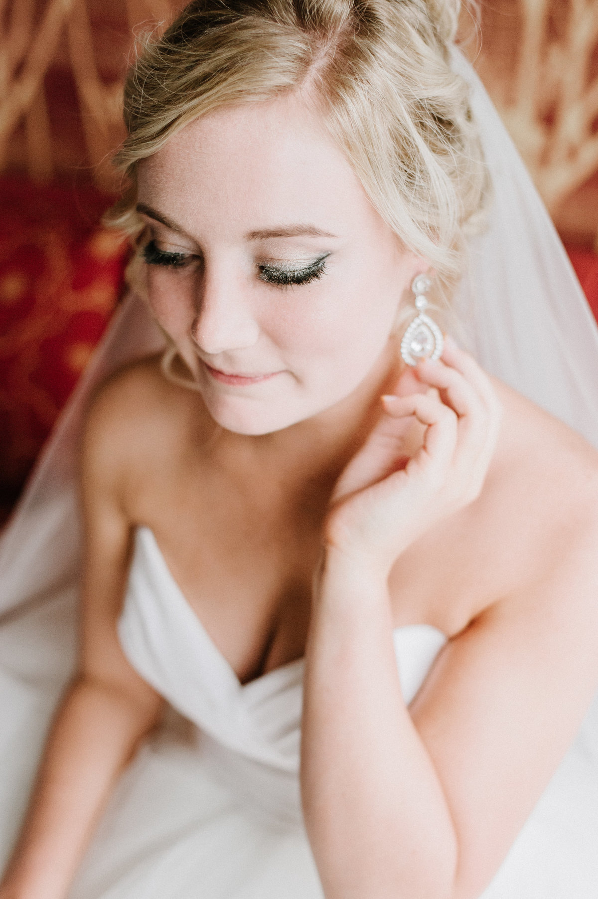 bride wearing strapless dress sitting on couch touching earring