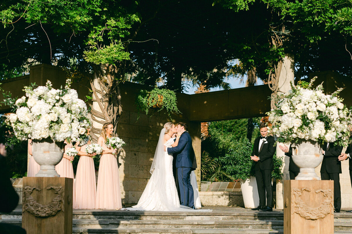 Bride and groom first kiss at ceremony altar Dallas Arboretum wedding