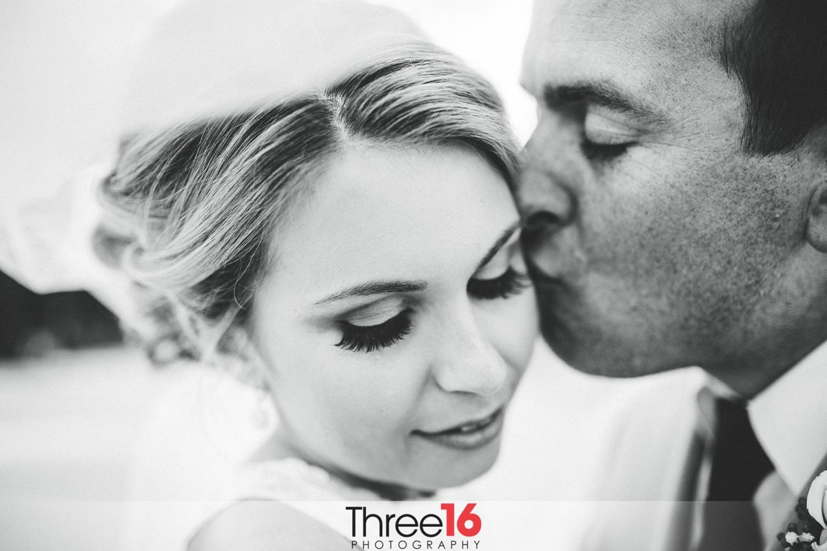 Brides receives a kiss on her cheek from her Groom
