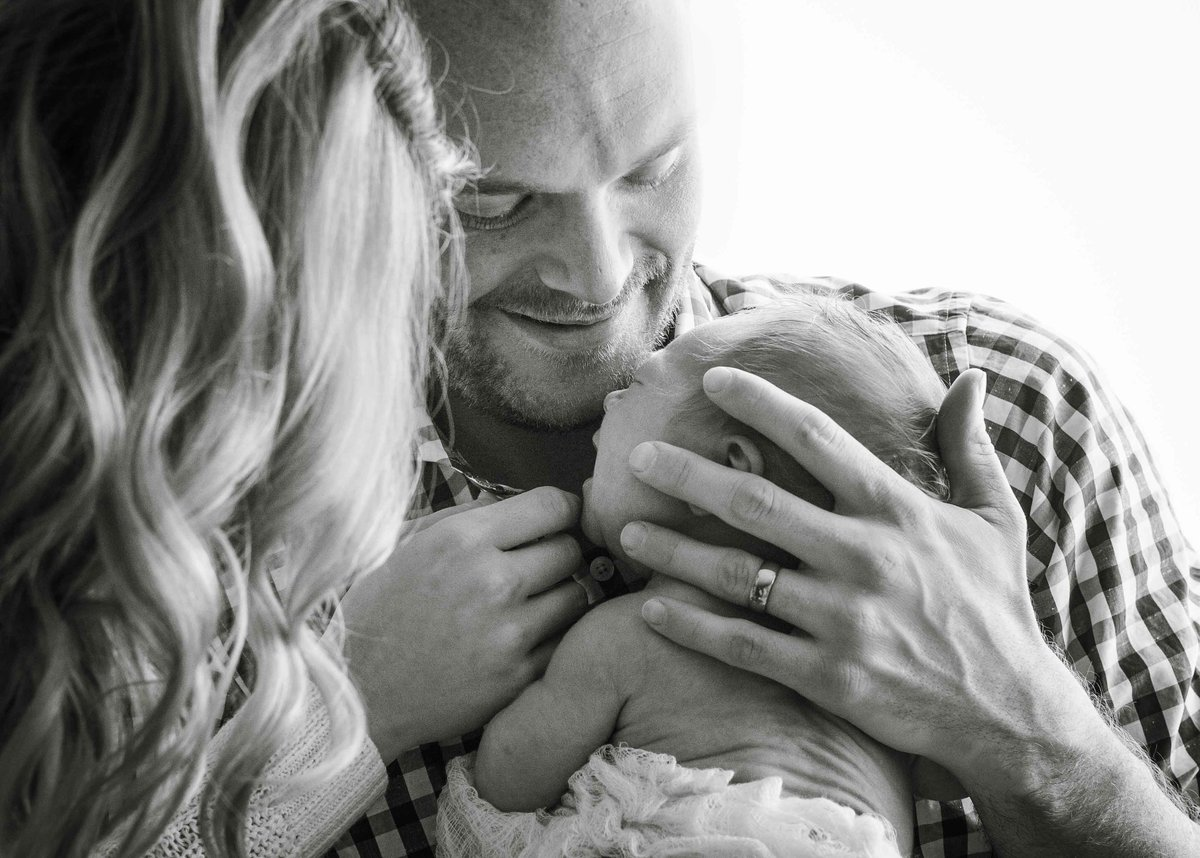 Sky 9 Studio | Documentary style black and white photo of new parents holding baby and comforting him during in-home lifestyle photo shoot